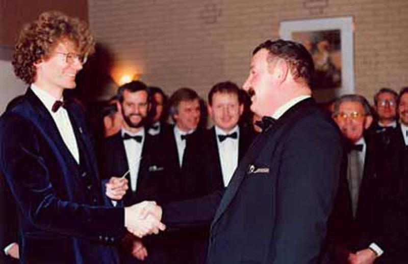 """Januari 1990: met het overhandigen van het dirigeerstokje """"installeert"""" voorzitter Roel Samplonius Nick Moritz als dirigent. Direct links van de voorzitter Ronald Pastoor, in 2015 bestuurslid van het koor."""