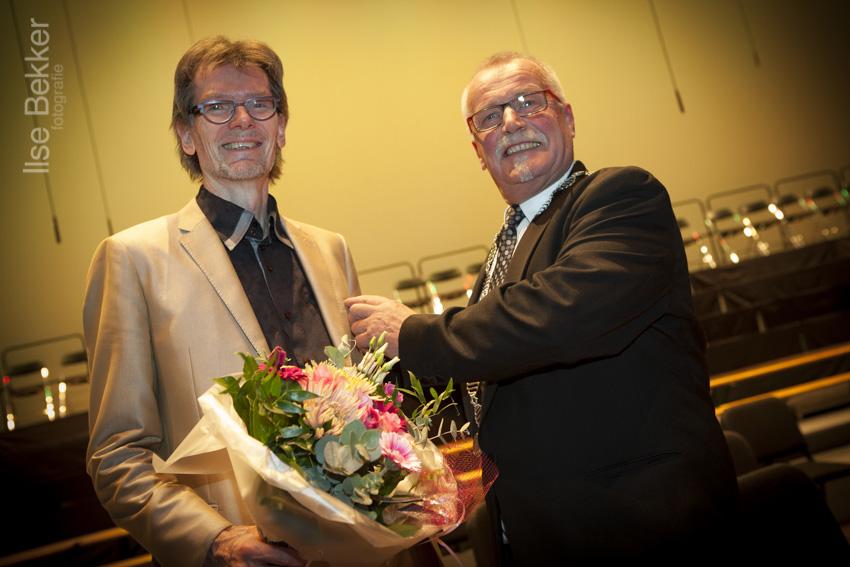 Koorlid Henk Hengeveld en loco burgemeester spelt Nick Moritz de koninklijke onderscheiding op