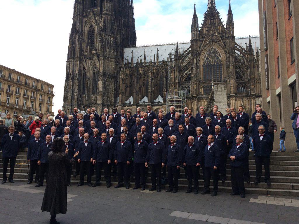 Het Ettens Mannenkoor zingt na de dankdienst aan de zijkant van de Dom, Armanda ten Brink dirigeert en dirigent Nick Moritz zingt links vooraan mee. Foto: Ewald Wormskamp